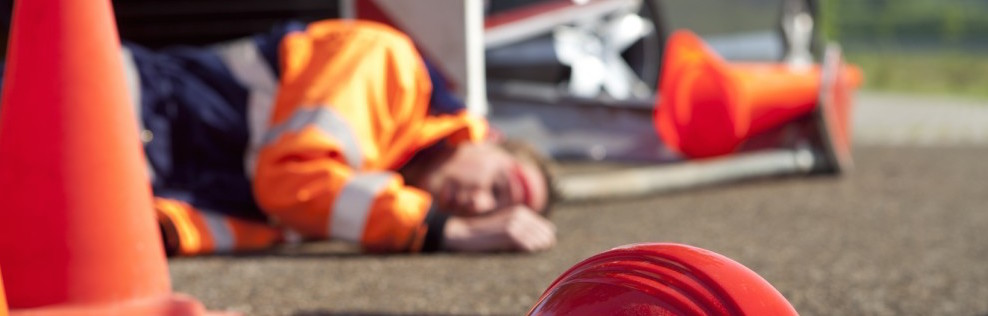 Man with a head injury laying on a road wearing PPE